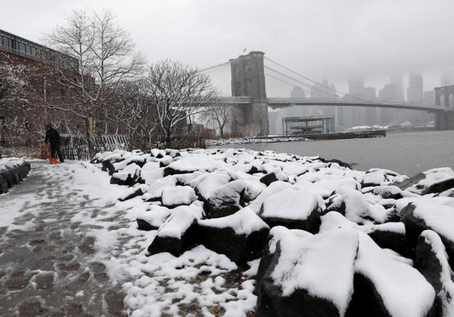 A woman shovels snow from a walkway at Brooklyn Bridge Park in New York, U.S., April 2, 2018