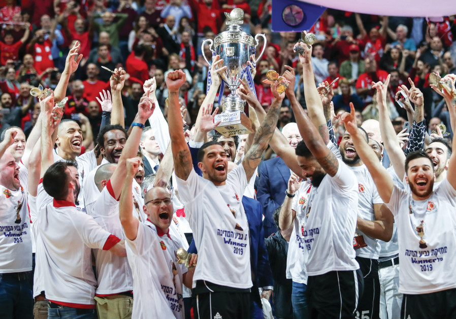 HAPOEL JERUSALEM celebrates on the court with the trophy following its victory