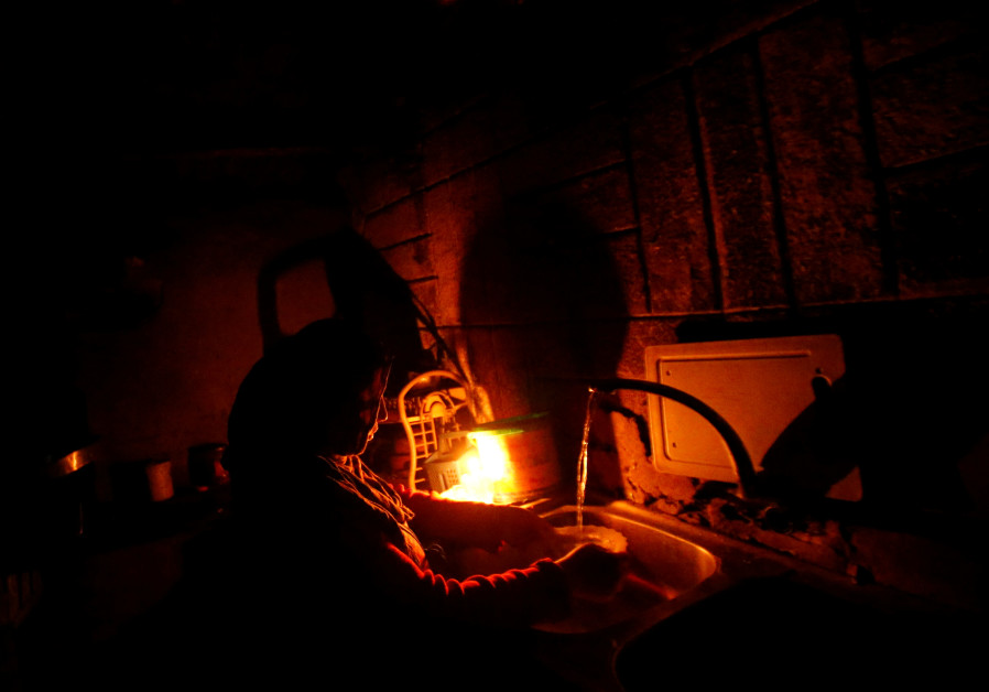A Palestinian woman uses a candle light as she washes up in her kitchen during a power cut inside he