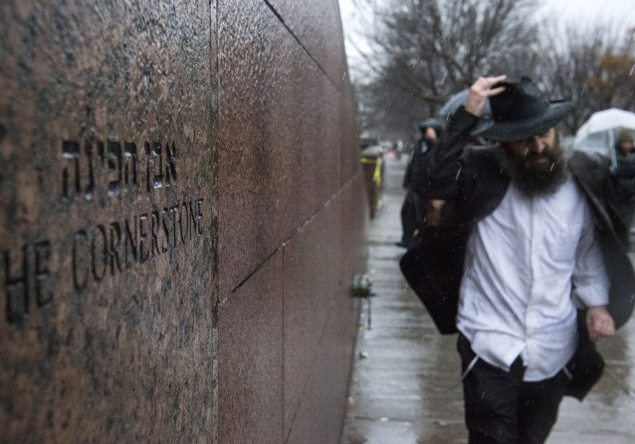 A man walks past the world headquarters of the Chabad-Lubavitch movement, the scene of a stabbing at