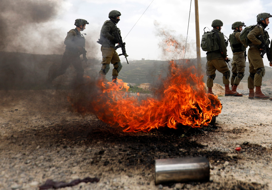 Israeli soldiers stand during clashes with Palestinians in the West Bank