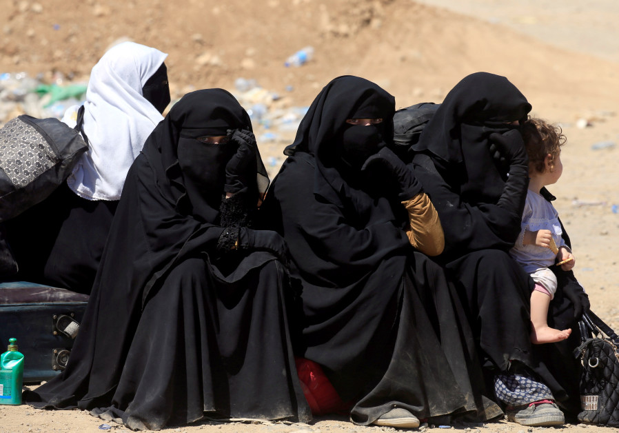 Displaced Iraqi women who fled from clashes sit together during a battle between Iraqi forces