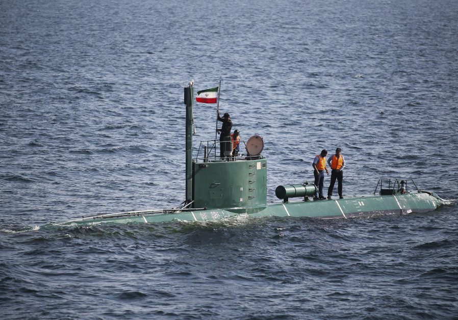 Military personnel place a flag on a submarine during the Velayat-90 war games by the Iranian navy i