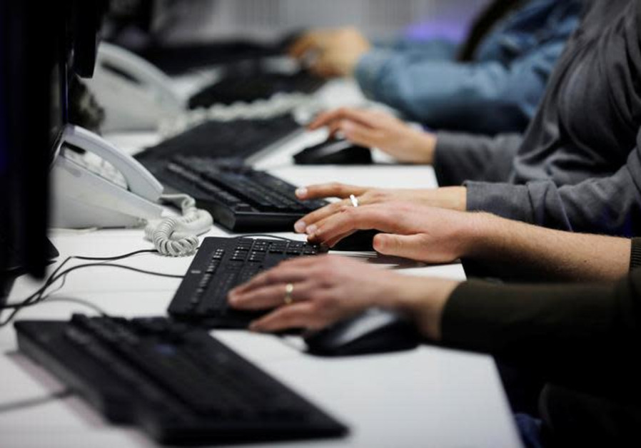 Employees, mostly veterans of military computing units, use keyboards working at a cyber hotline