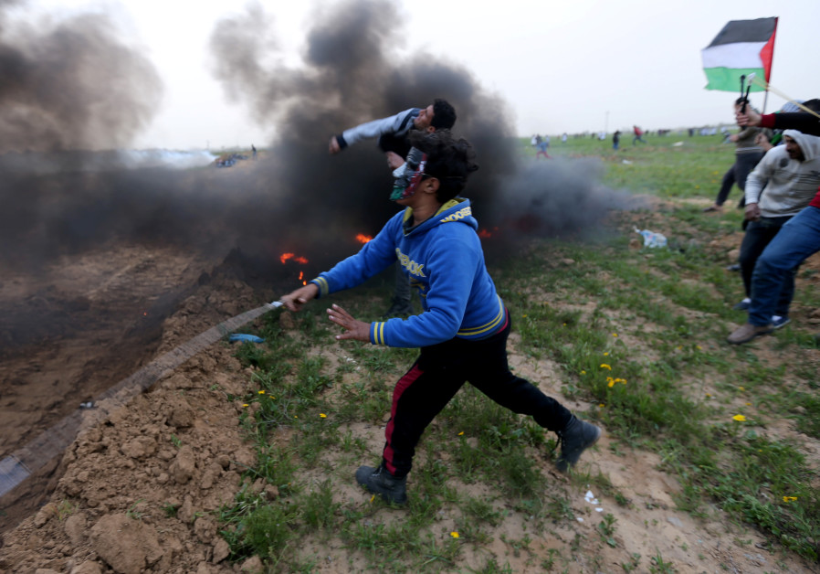 Palestinians hurl stones at Israeli troops during a protest at the Israel-Gaza border fence, in the