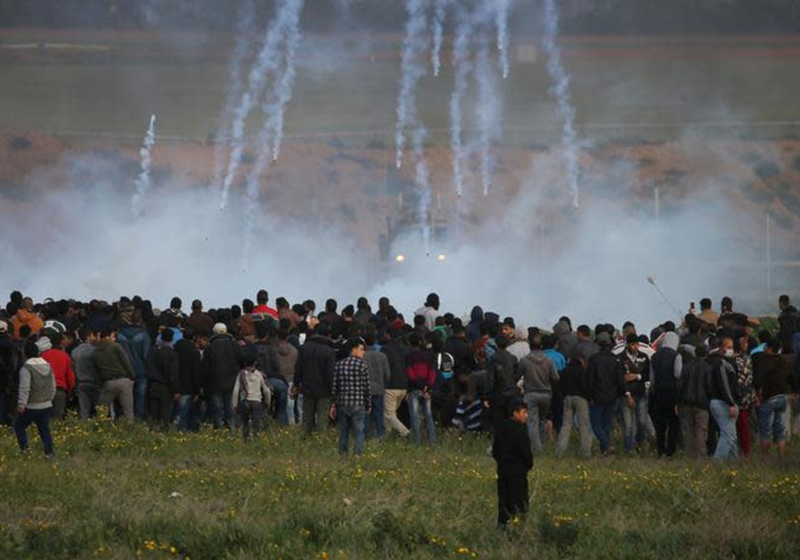 Tear gas canisters are fired by Israeli troops toward Palestinians during a protest