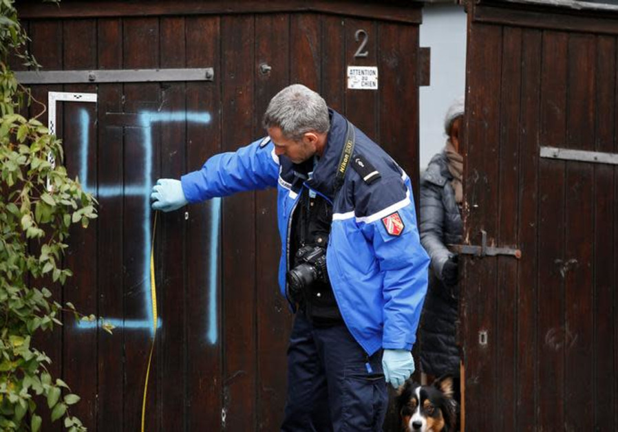 A French gendarme inspects a door that is desecrated with a swastika near the Jewish cemetery