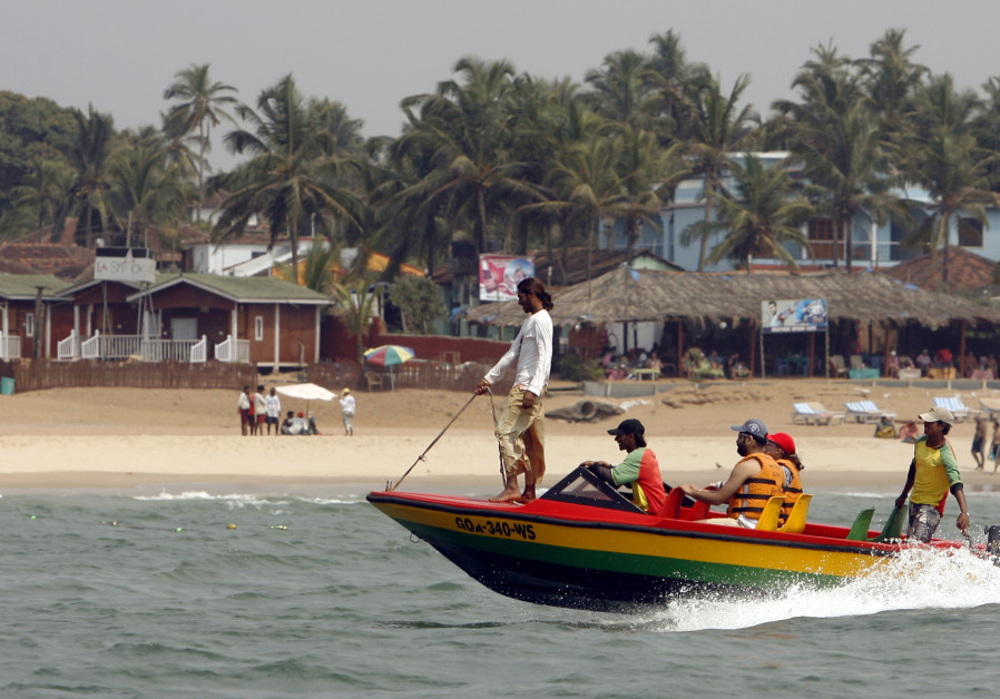 Tourists ride a boat at the Anjuna beach in the western Indian state of Goa March 14, 2008.