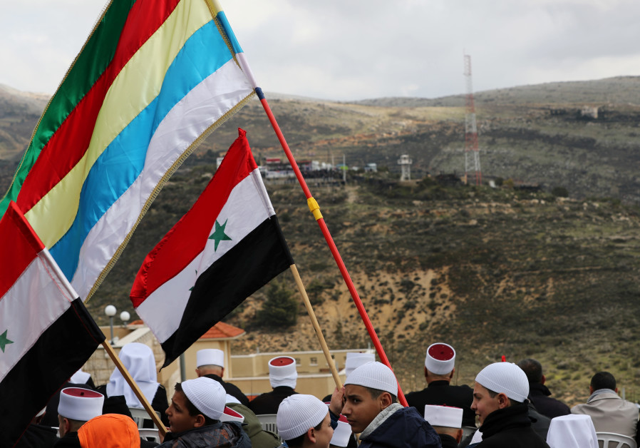 Members of the Druze community holds Syrian and Druze flags as they sit facing Syria, during a rally