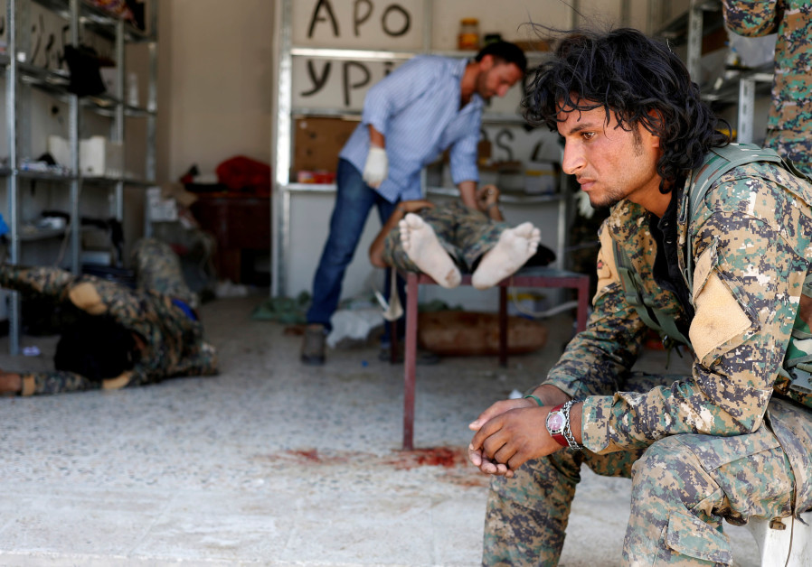 A Syrian Democratic Forces (SDF) fighter sits as medics treat his comrades injured by sniper fire
