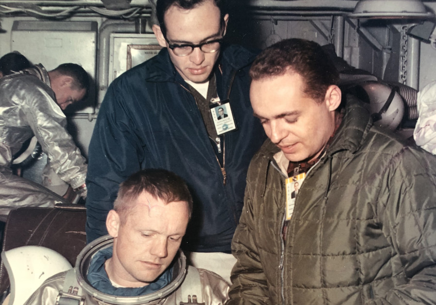 Neil Armstrong (foreground) inspects space suit gloves with Dr.Gerald Ahronheim (R)