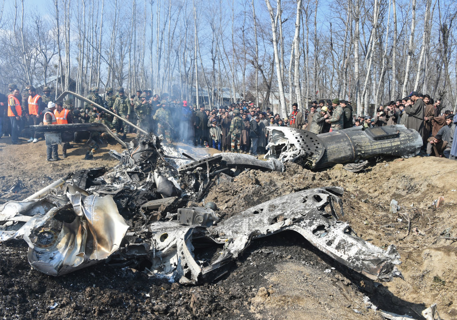 Indian soldiers and Kashmiri onlookers stand near the remains of an Indian Air Force aircraft
