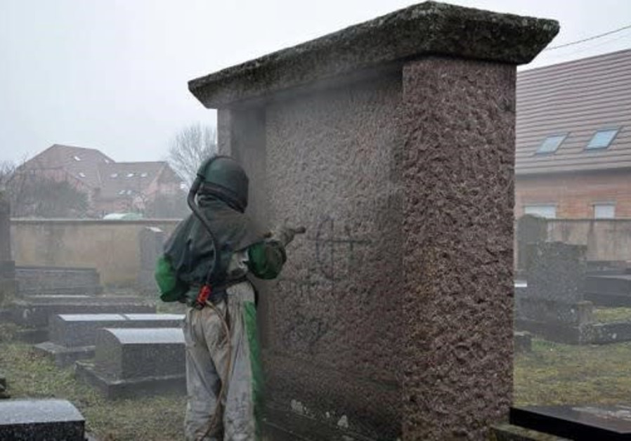 A worker removes antisemitic graffiti at a Jewish cemetery in France, March, 2019