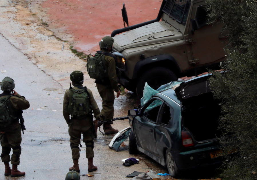 Israeli forces stand at the scene of a car ramming in the West Bank that injured two soldiers, March