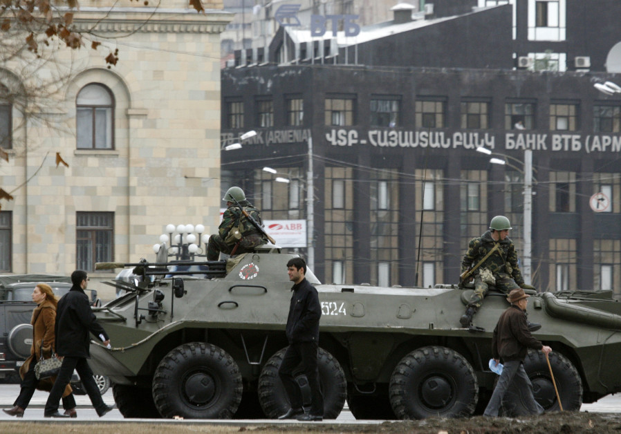 People walk past an armoured vehicle in central Yerevan March 3, 2008.