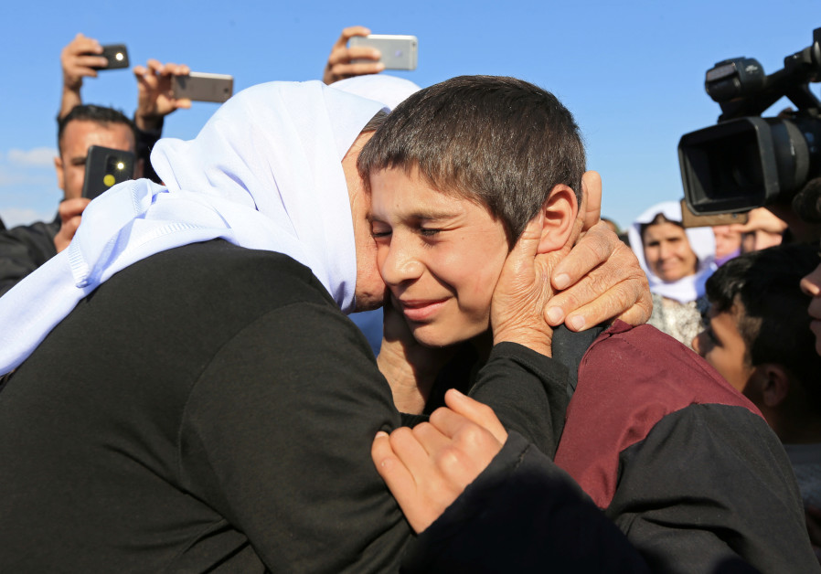 A relative kisses a Yazidi survivor boy following his release from Islamic State militants in Syria.
