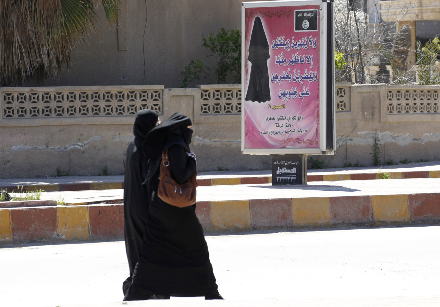 Veiled women walk past a billboard urging women to wear a hijab in Raqqa(REUTERS/Stringer)