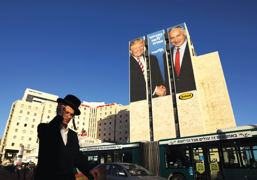 A MAN walks past a Likud election campaign billboard, depicting US President Donald Trump with Prime