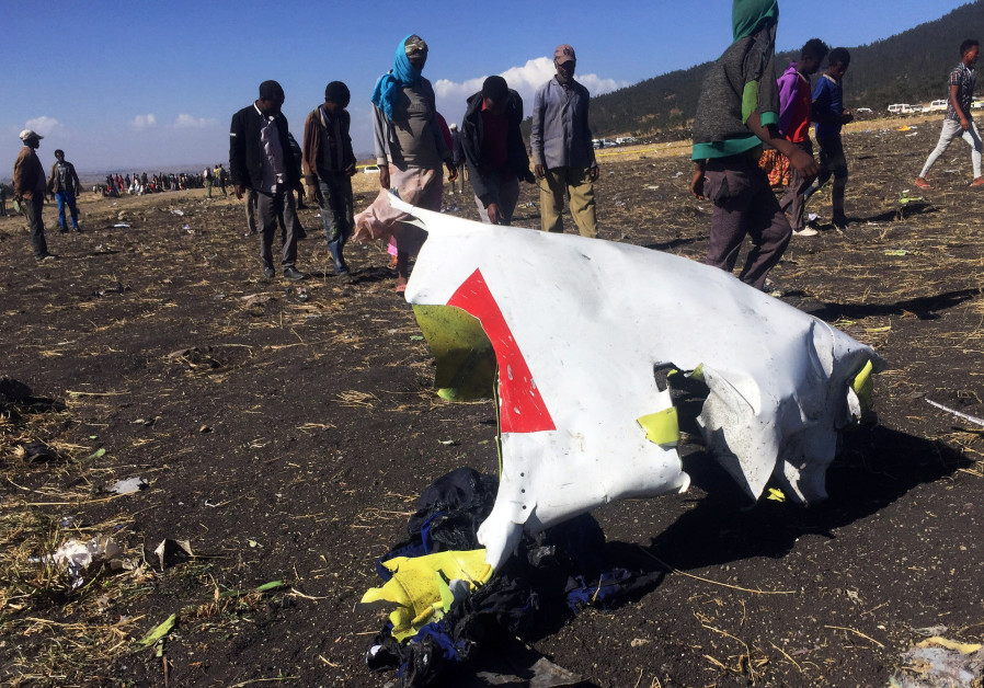 People walk past a part of the wreckage at the scene of the Ethiopian Airlines Flight ET 302 plane