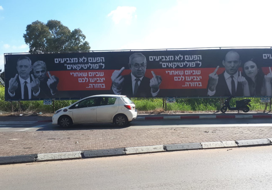 Billboards, doctored to show top politicans giving the middle finger, in central Israel, March, 2019 (Eli Eliyahu)