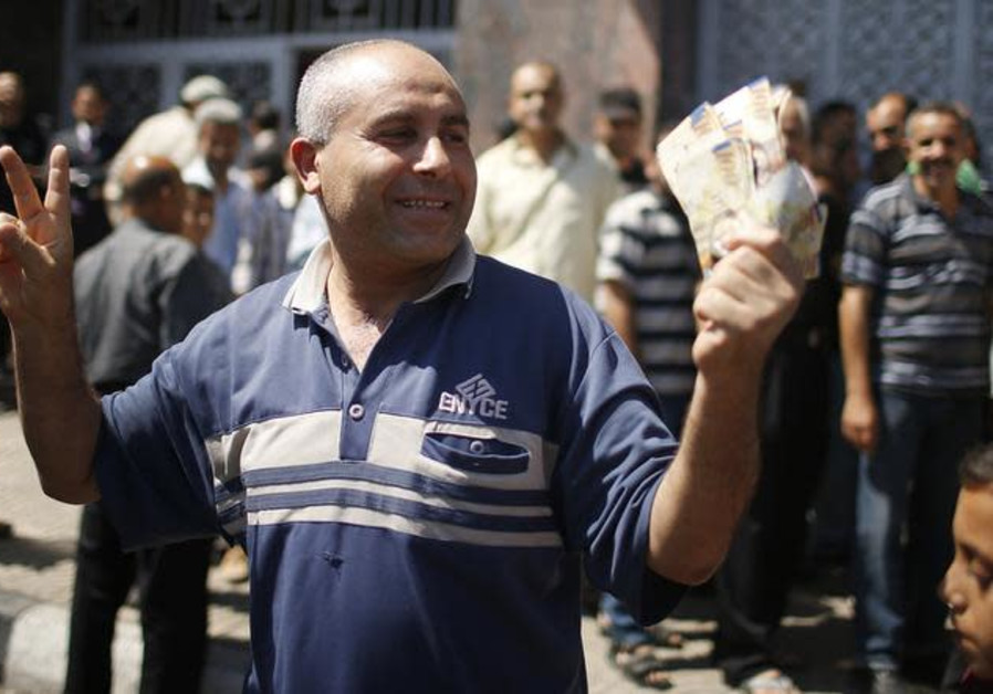 A Palestinian employee paid by the Palestinian Authority gestures as he holds money