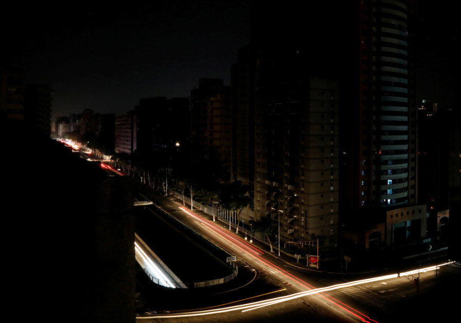 Car lights are seen on one of the main roads of the city during the second day of a blackout in Cara