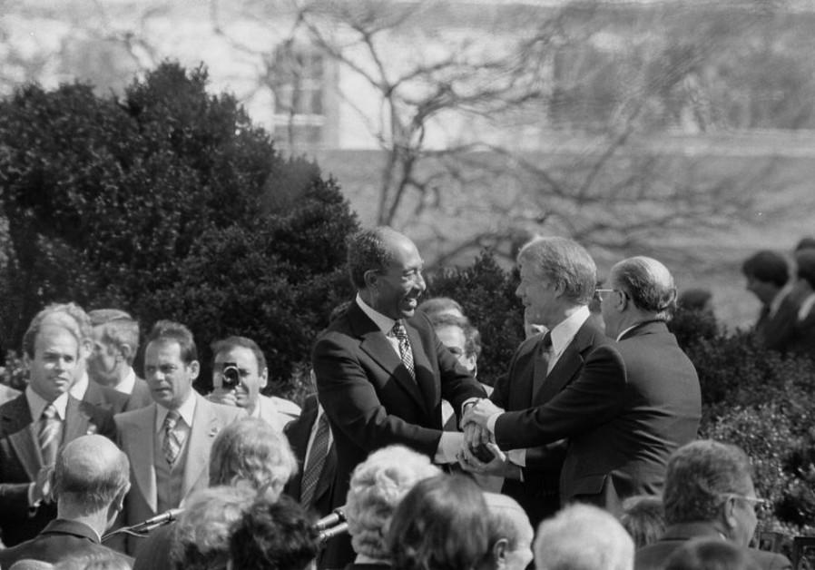 President Jimmy Carter shakes hands with Egyptian President Anwar Sadat and Israeli Prime Minister M