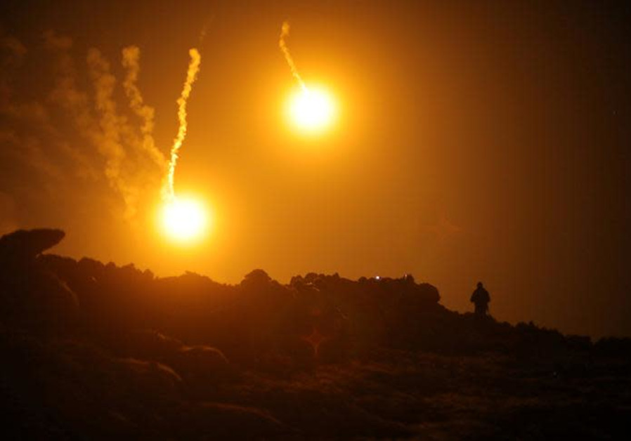 Flares are seen in the sky during fighting in the Islamic State's final enclave