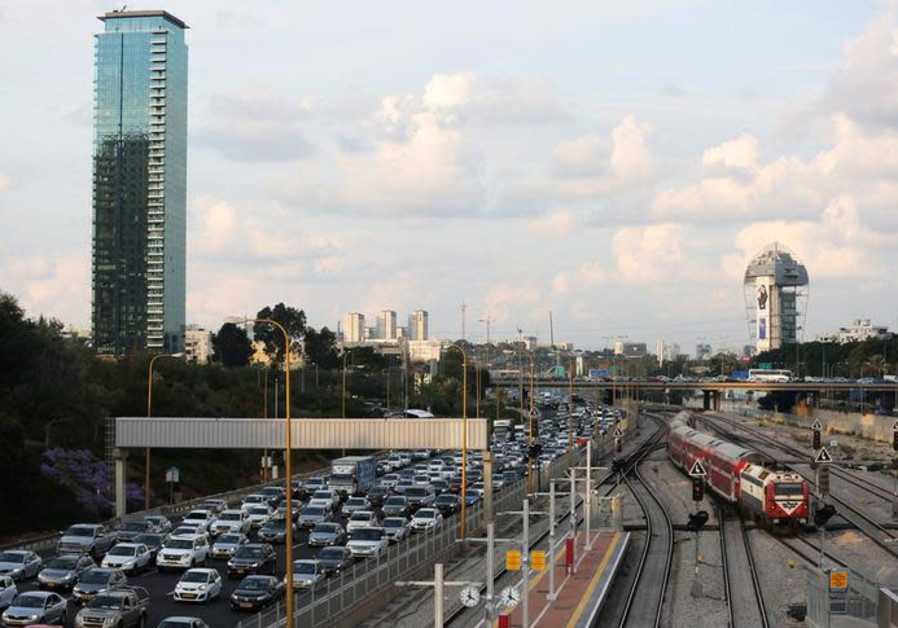 Cars drive on a highway as a train enters a station in Tel Aviv, Israel November 25, 2018