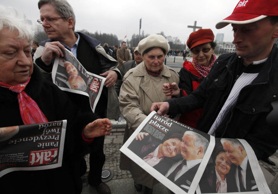 A man distributes special editions of a newspaper in front of the Presidential Palace in Warsaw