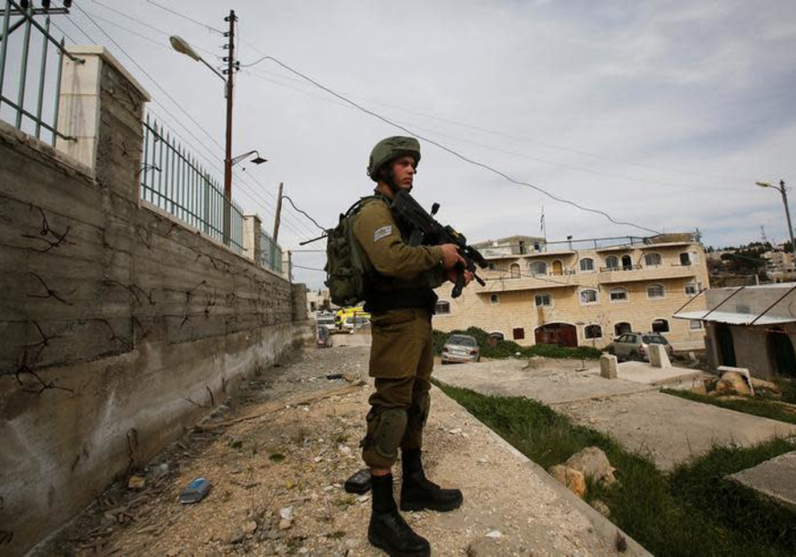 An Israeli soldier stands guard in Hebron