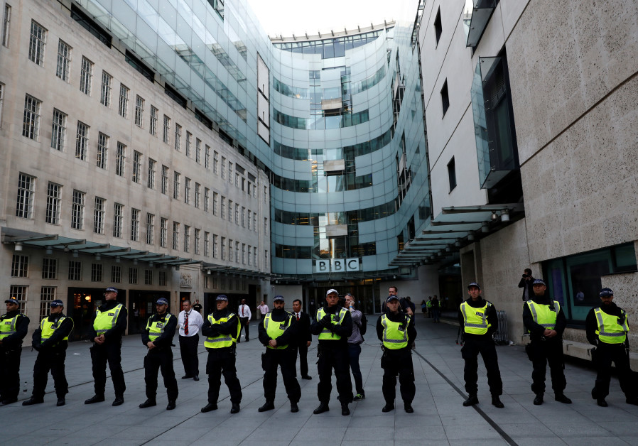 Police officers protect the entrance to the BBC building