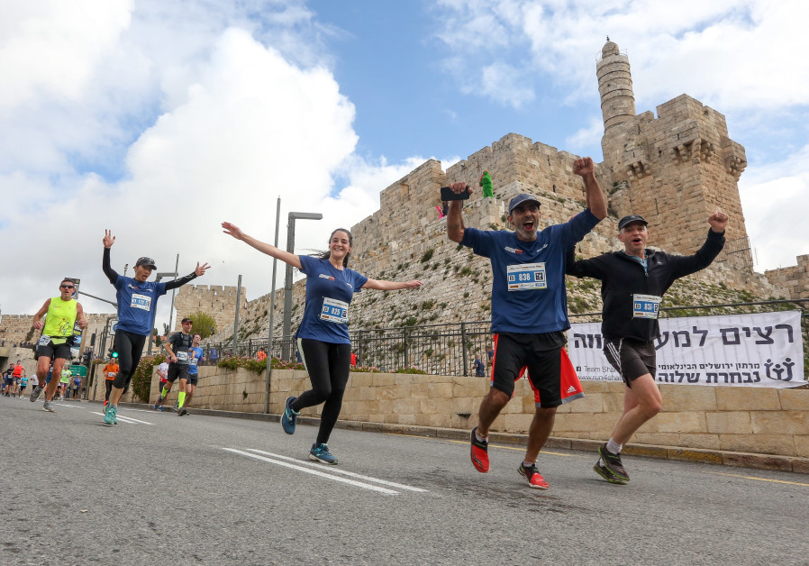 Jerusalem Marathon runners run past the Jerusalem's Old City walls, March 15th, 2019