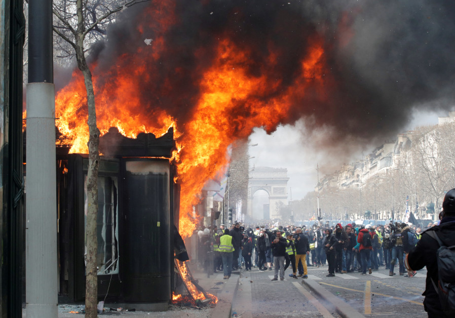 """A burning newsagent's shop is seen during a demonstration by the """"yellow vests"""" movement in Paris"""