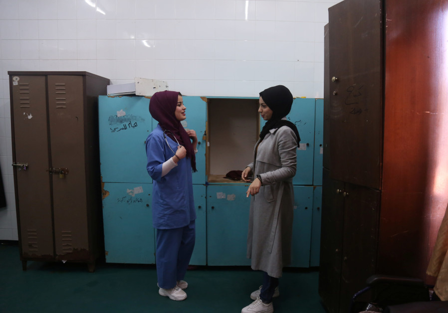 Palestinian midwife Sara Abu Taqea (L), 23, who works in the maternity ward at Gaza's Al-Ahli hospit