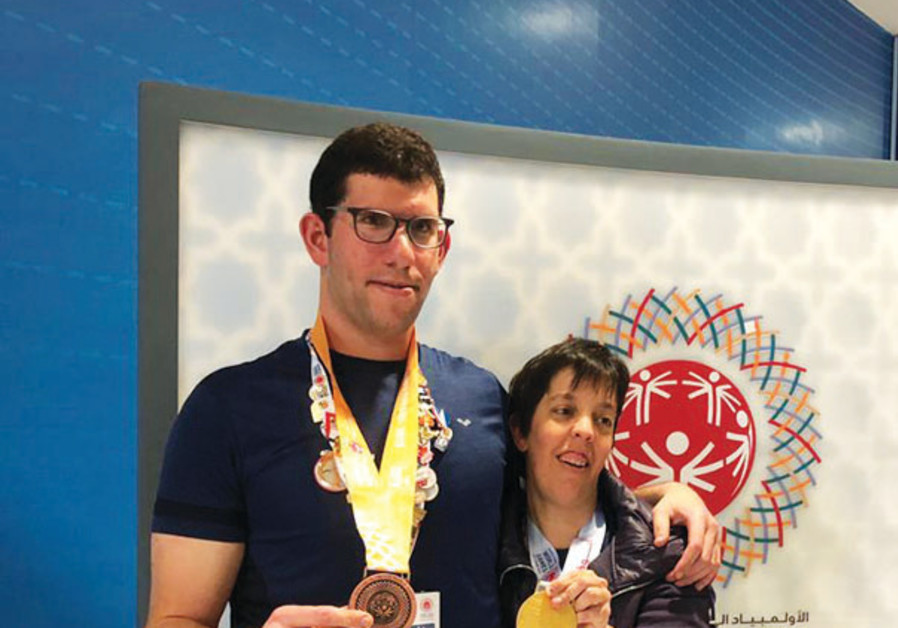 ISRAELI SWIMMERS Gilad Kalishov (left) and Avital Naveh (right) pose with the medals that they won
