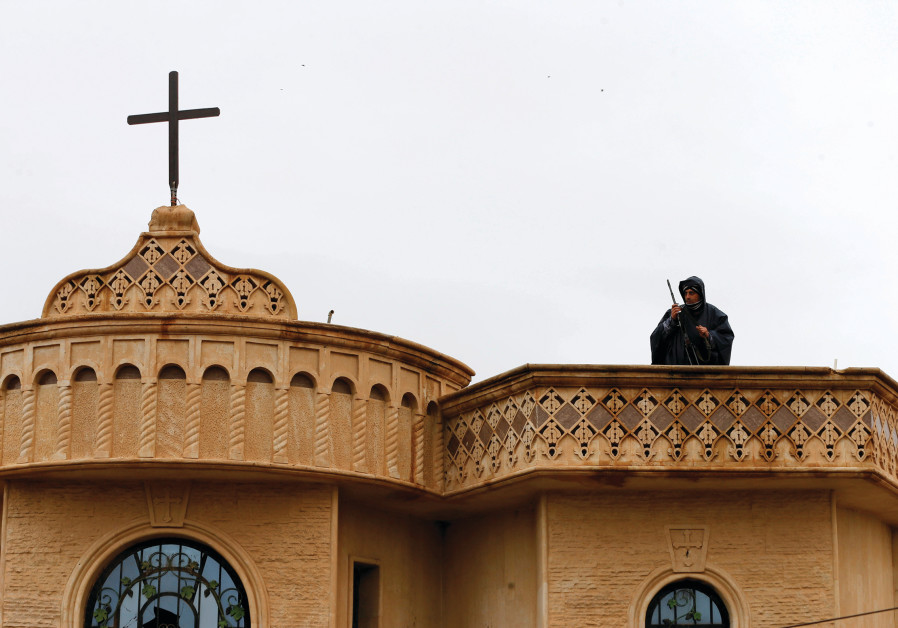 A SECURITY forces member stands atop a church in Bartella