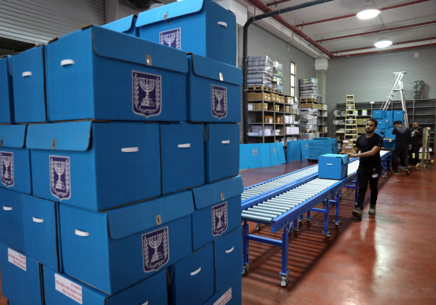 People sort ballot boxes as part of preparations for the upcoming Israeli election