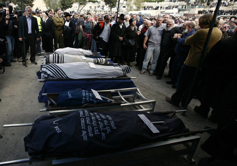 Mourners stand around the bodies of Ehud Fogel, 36, his wife Ruth, 35, and their children