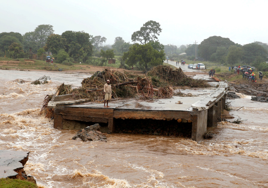A man looks at a washed away bridge along Umvumvu river following Cyclone Ida