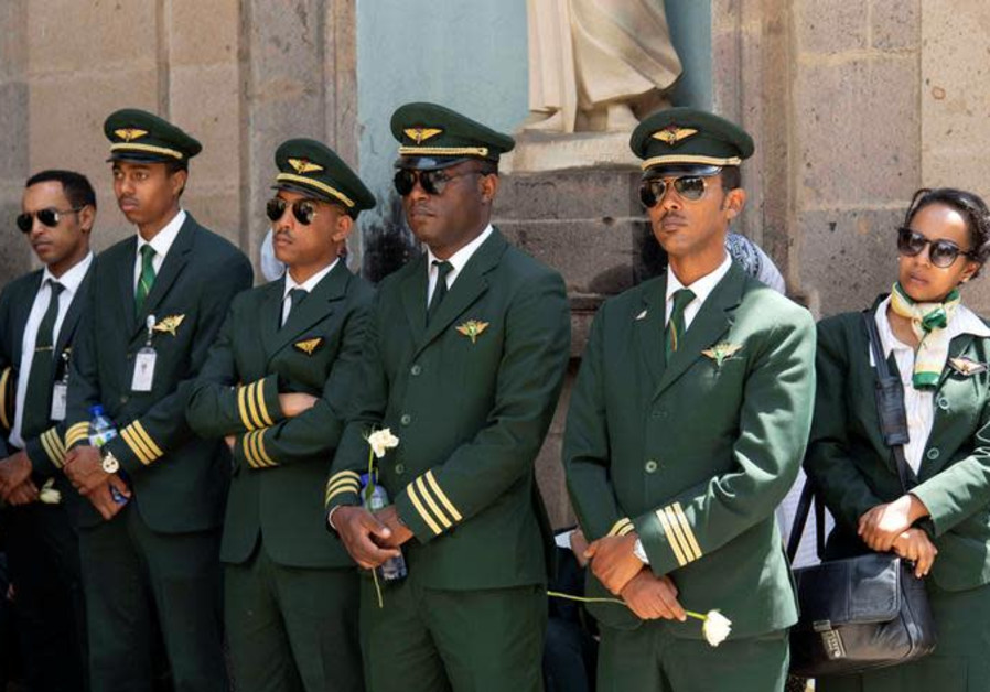 Ethiopian Airlines crew members mourn as pallbearers carry the coffins of their colleagues