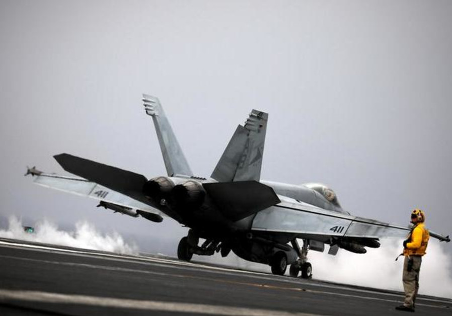 An F/A-18 fighter jet takes off from the USS Harry S. Truman aircraft carrier in the eastern Mediter