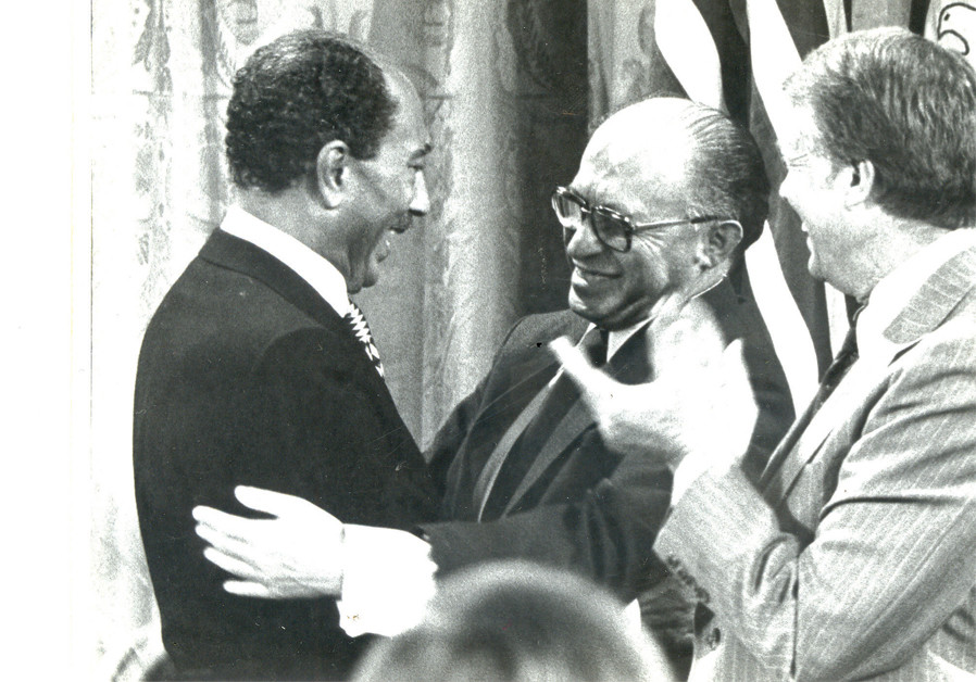 Egyptian president Anwar Sadat and prime minister Menachem Begin clasp hands with US president Jimmy Carter after the landmark 'Framework for Peace in the Middle East' was signed on the White House lawn. (Moshe Milner/GPO)