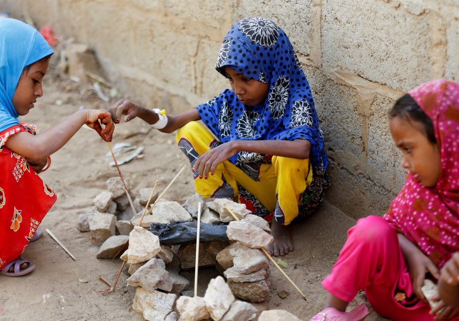 Afaf Hussein (C), 10, who is malnourished, plays with other girls near her family's house in the vil