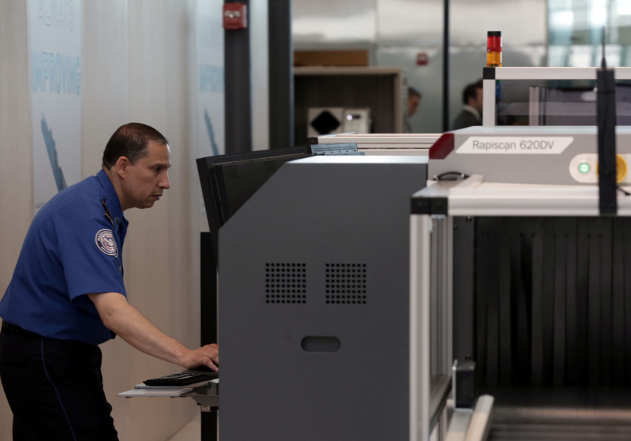 A Transport Security Administration employee scans baggage using new Automated Screening Lane techno