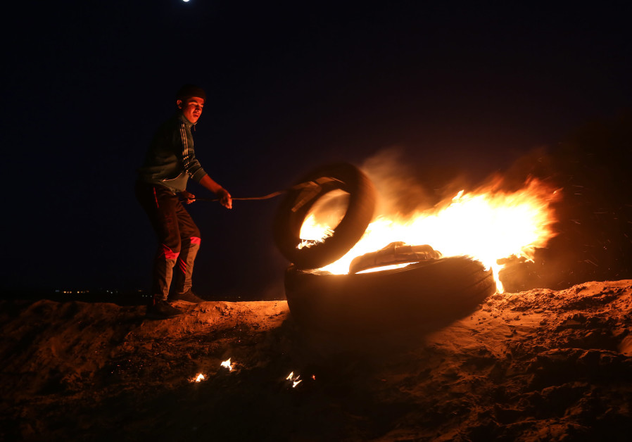 Palestinian protesters take part in a night demonstration near the fence along the border