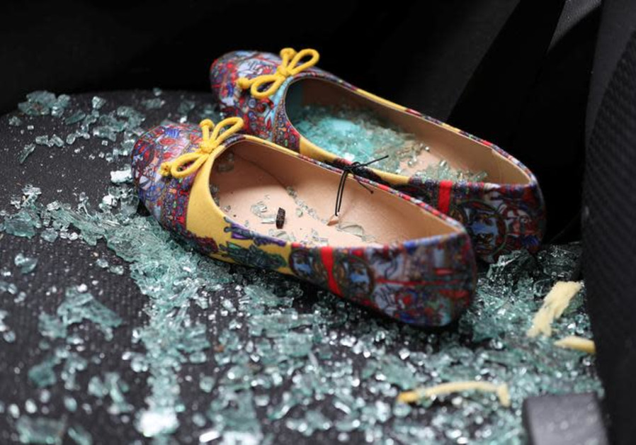 Shattered glass covers shoes left on the seat of a car that was damaged after a rocket hit a house