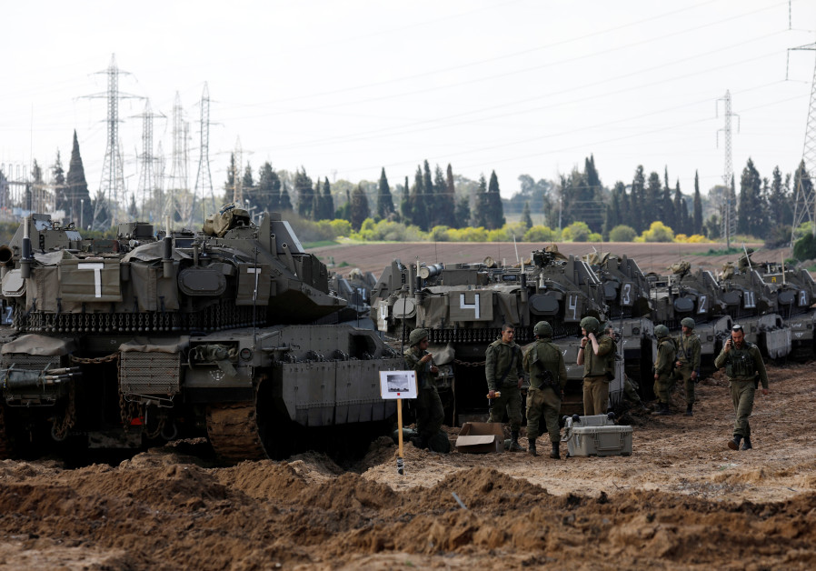 Israeli soldiers chat next to armored personnel carrier's (APC) near the border with Gaza, in southe