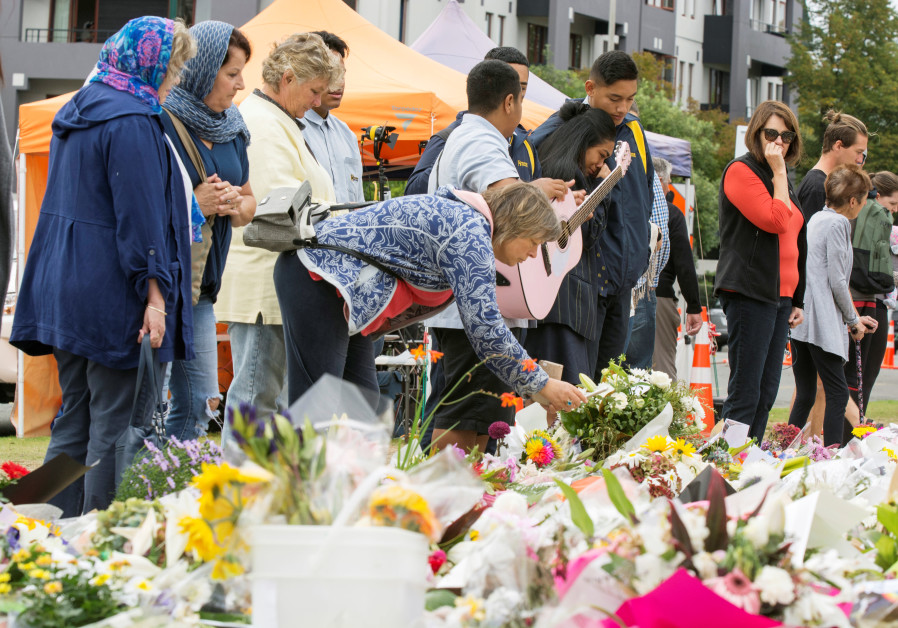 People place flowers near the police cordon for the Linwood Islamic Centre