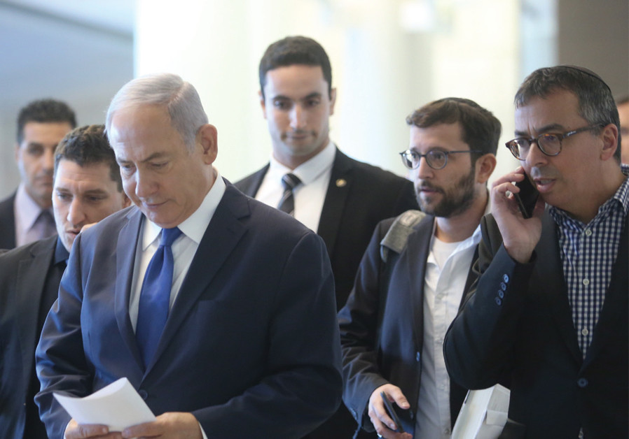 Yonatan Urich stands to the right and a bit behind PM Netanyahu while walking in the Knesset (credit: Marc Israel Sellem)